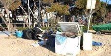 Immagine Discarica sulla spiaggia tra i rifiuti un congelatore