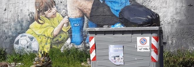 Napoli, un cassonetto davanti al murales di Maradona