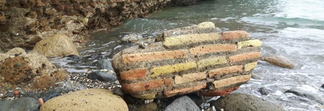Baia: dopo la mareggiata, rifiuti e pezzi della città sommersa invadono la spiaggia