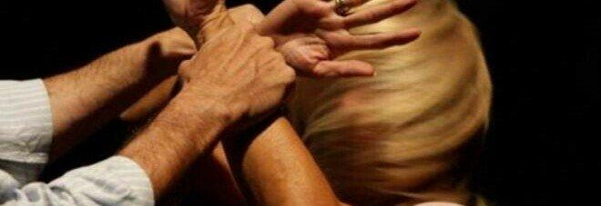 Calci e pugni alla moglie mentre ha in braccio il figlio piccolo
